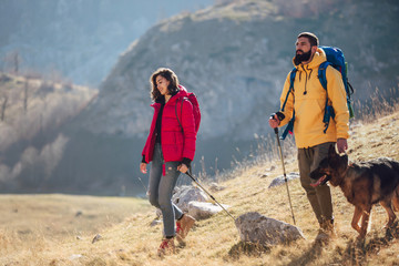 Couple of hikers walking on a mountain at autumn day.