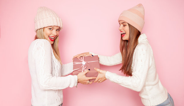 Two cute woman with red lips and hats sharing gift between themselves. Concept Christmas and New Year. Pink background