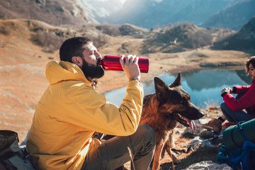 Group of people taking a break, relaxing during a hike. Man drink water.