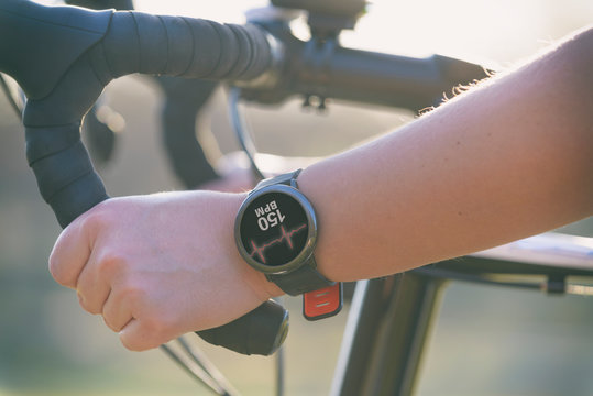Woman riding a bike with smartwatch heart rate monitor