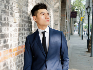 Portrait of a handsome businessman in suit posing outdoor, close up upper body view. Attractive male hipster Chinese model.