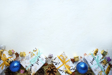 Christmas background with gifts and pine cones. View from above.