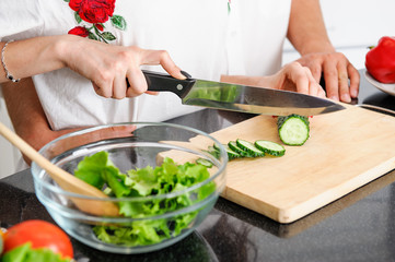 young man and woman hands cooking healthy vegetarian food from fresh vegetables