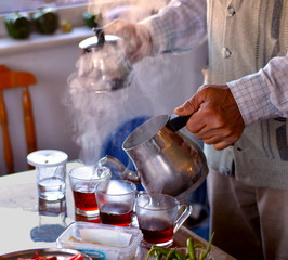 Hands of senior man with metal Turkish teapot pouring tea into glass cups for breakfast. Old Turkish man pouring tea.