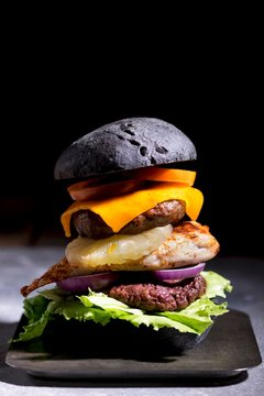 Beef, Chicken and Pork burgers with melted cheese in a black bun