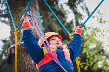 little girl climbing in adventure activity park