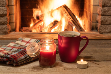Cozy scene against fireplace with a Red mug with tea and a candle.
