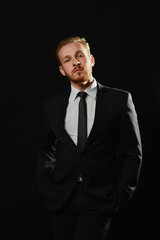 Handsome bodyguard with beard in formal wear standing on black background. Gambling business concept.