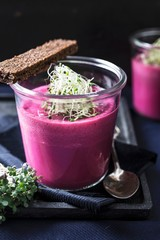 Beetroot and apple soup in a glass with onions and shoots, served with pumpernickel bread and mustard cress