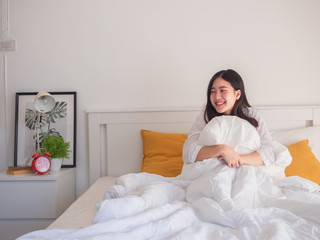 asian women embrace pillows on bed in the morning