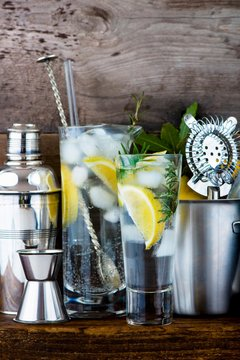 Gin and tonic with lemon, ice cubes and rosemary between various bar utensils