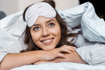 smiling dreamy girl in sleeping mask resting under blanket on bed
