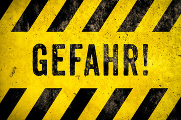 GEFAHR! (in German, danger) warning sign text with yellow and black stripes painted over concrete wall cement texture wide banner background. Concept image for caution, dangerous area and hazard.