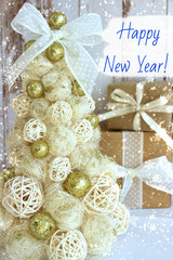 New Year, Christmas background, rustic style. Festive Christmas tree in gold on white wood background and craft boxes tied with satin ribbons. Beautiful Christmas tree with Golden balls, frame of whit