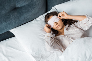 young woman in sleeping eye mask waking up in bed in the morning