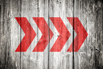 Red directional arrow signs pointing direction over old grungy and weathered white and grey painted wooden wall plank texture background with vignetting add dark corners with retro vintage look.
