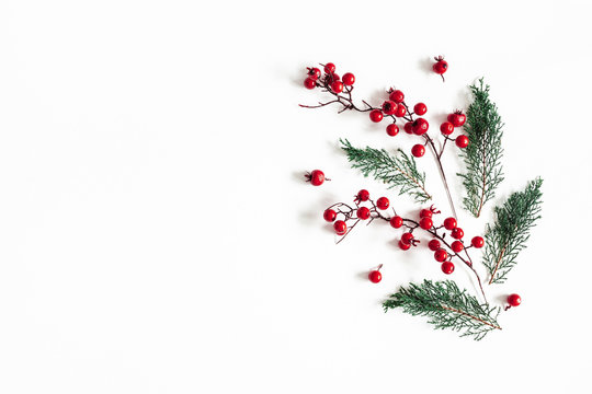 Christmas composition. Pattern made of fir tree branches and red berries on white background. Christmas, winter, new, year, nature concept. Flat lay, top view, copy space