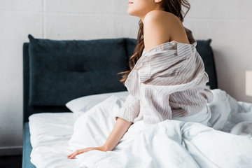 cropped view of tender woman in pajamas sitting on bed in the morning