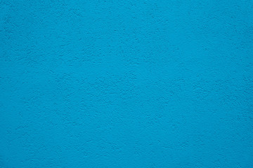Blue cyan wall background. Grain stucco wall from a house coarse exterior facade as an empty rustic and simple blue surface texture background.