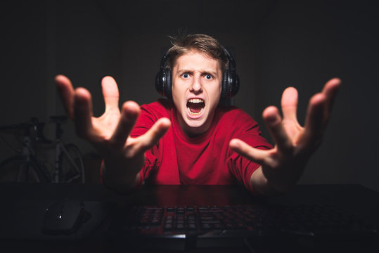 Gamer lost in the online video game, so angry. Portrait of an evil gamer playing games at night on a computer and emotional looking at the camera. Gamer concept