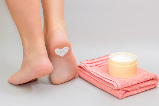 Beautiful female legs with heart from ointment cream on heel. Woman girl applying moisturizer cosmetic cream on foot. Health skin care.