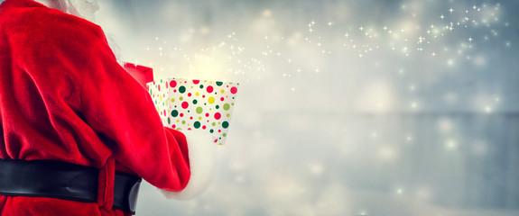 Santa opening a gift box on a shiny light background