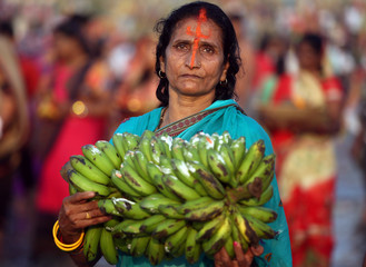 A Hindu woman holds bananas as she worships the Sun god in the waters of the Arabian Sea during the religious festival of Chhath Puja in Mumbai