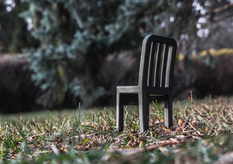A beautiful small toy black plastic chair is on a blurred background