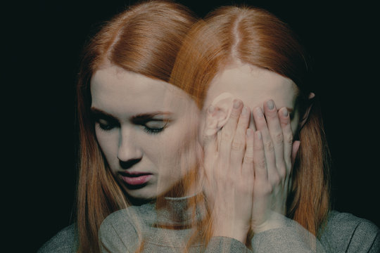 Porter of beautiful redhead girl with psychotic disorders covering her face, hiding from her hallucinations
