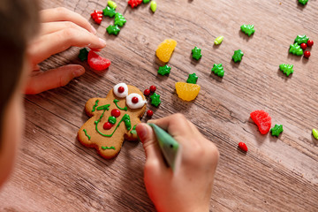 child decorates gingerbread cookie. the gingerbread man on a wooden table. the concept of preparation for Christmas