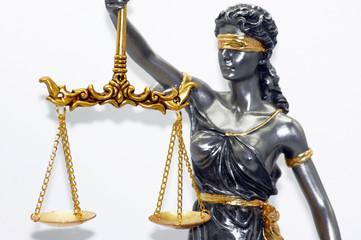 Nahaufnahme einer Justiz Figur freigestellt auf weißem Hintergrund