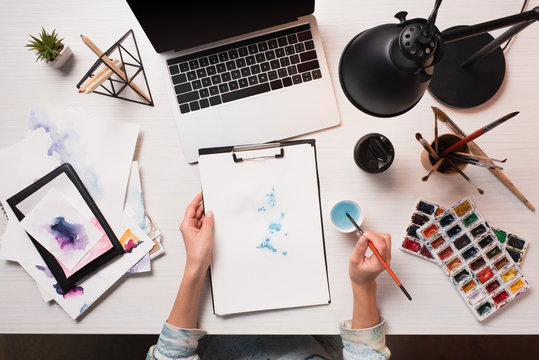 office desk with laptop, art supplies and cropped view of designer drawing, flat lay