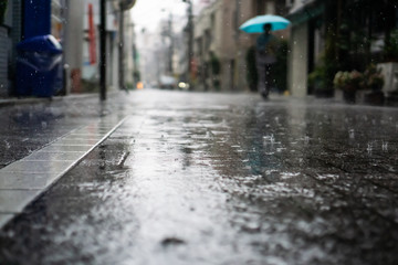 Rainy day in a city with people walking on sidewalk and holding Umbrellas in the background (Bunkyo district, Tokyo, Japan)