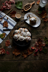 Autumn dessert cinnamon buns with cream cheese on board with leafs