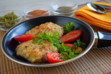 Delicious fried cutlets with tomatoes and herbs in a frying pan.
