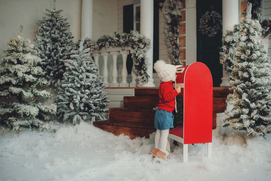 A little baby girl in a white knitted hat makes a wish and writes a letter to Santa Claus and sends a postcard by mail. Throws envelope in the mailbox