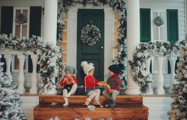 A portrait of children sitting on the porch of their house together, Eat bagels. Merry Christmas, happy New Year. Yard with a christmas tree, lights and decorations. Miracle time.