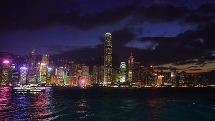 Fototapete - Footage of Skyscrapers and floating ship at Victoria's harbor, Hong Kong at night. 4K