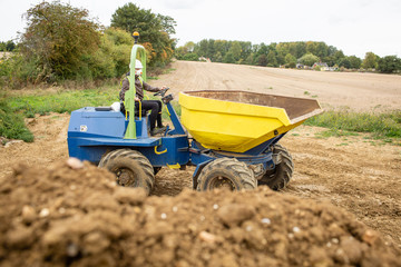 Yellow front tipper dumper working in construction site. Soil pile in foreground.