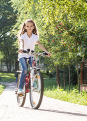 Cute girl riding her bike in the park in the sun.