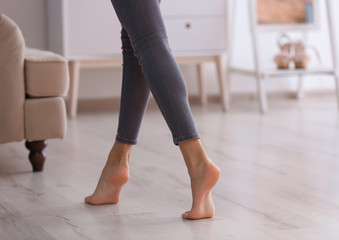 Young woman walking barefoot at home, closeup. Heating concept