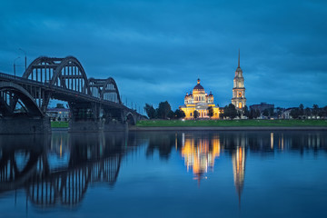 Fototapete - Rybinsk, Russia. Spaso-Preobrazhenskiy cathedral and bridge over Volga river reflecting in water at dsuk