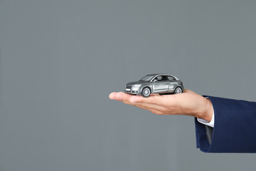 Insurance agent holding toy car on gray background, closeup