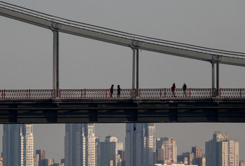 People are seen standing on the Parkovy Pedestrian Bridge over the Dnipro River in Kiev