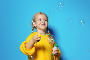 Cute little girl blowing soap bubbles on color background. Space for text