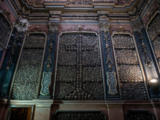 Large pile of real human skulls and bones stacked on a wall to form a christian cross in the ossuary of the church San Bernadino alla Ossa in Milan, Italy