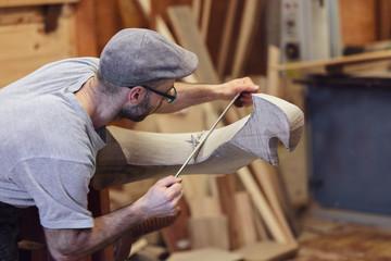 Carpenter working on wooden forcola for venetian gondola