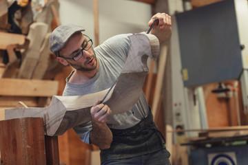 Photo sur Plexiglas Gondoles Carpenter working on wooden forcola for venetian gondola