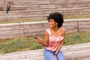 beautiful young afro american woman taking a picture with mobile phone, Sitting on wood stairs and smiling. wood background. Lifestyle outdoors