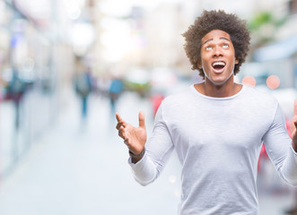 Afro american man over isolated background crazy and mad shouting and yelling with aggressive expression and arms raised. Frustration concept.